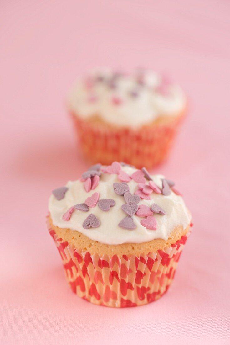Cupcakes mit Cremehaube und dekoriert mit Zuckerherzen