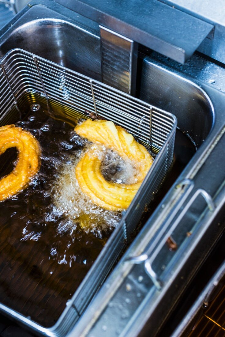 Churros in a deep fat fryer with oil