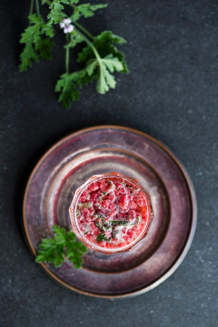 A beer cocktail with raspberry and scented pelargonium (seen from above)