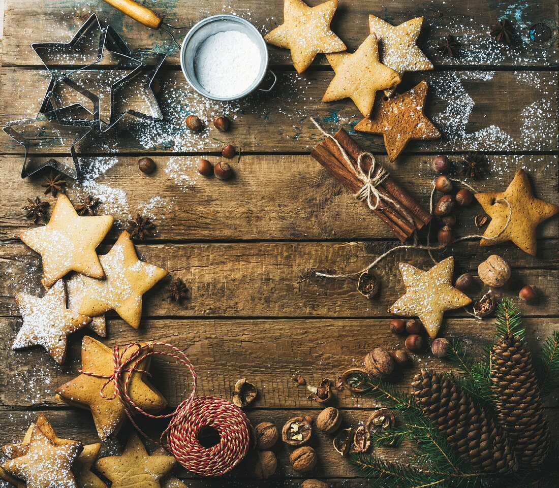 Star shaped sweet gingerbread cookies with sugar powder, nuts, cinnamon, anise, fir tree branch and pine cones