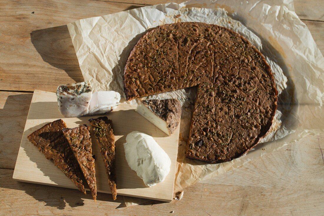 Ticino chestnut flour cake (castagnaccio) with rosemary, served with lard and ricotta