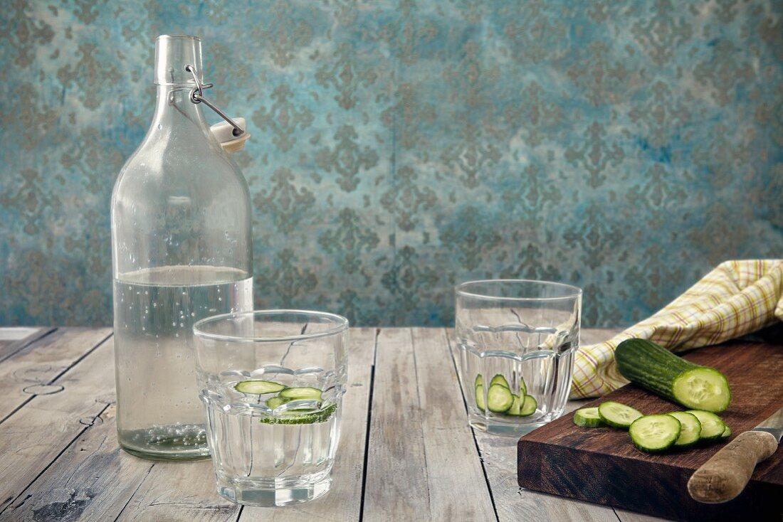 Glas Gurkenwasser, Wasserflasche und frische Gurke