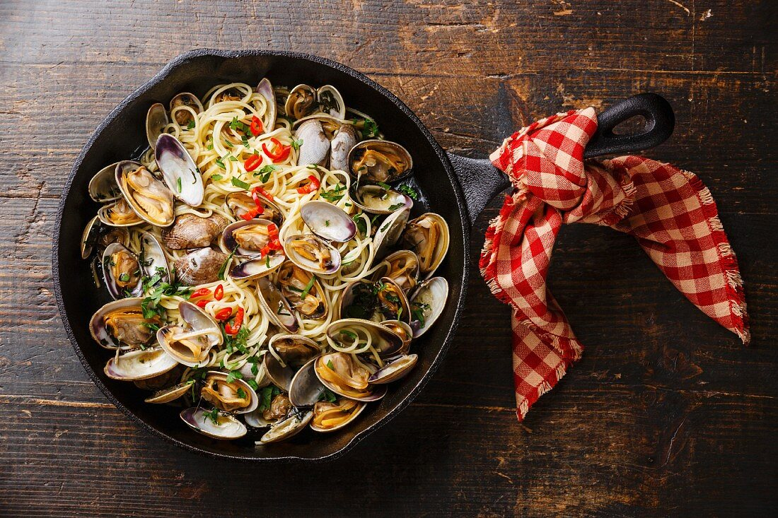 Spaghetti alle Vongole Seafood pasta with clams in cast iron frying pan on wooden background