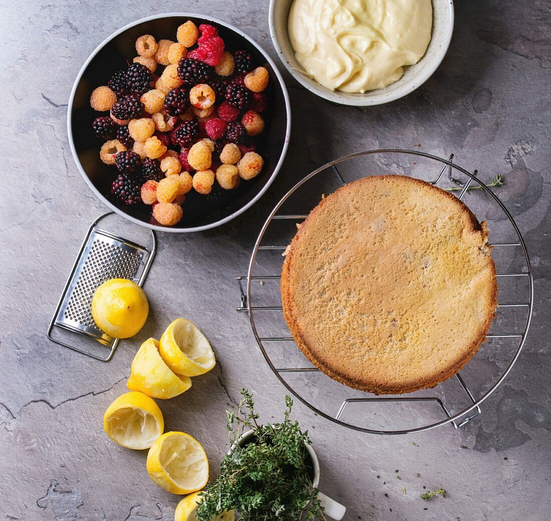 Bowls with ingredients for making sponge cake with lemon cream, yellow and red raspberries and dewberries and thyme