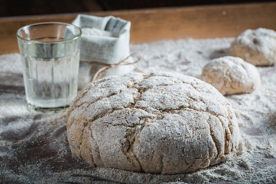 Unbaked loaves of bread and bread rolls with ingredients and flour