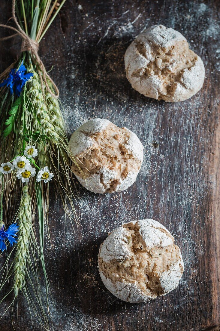 Healthy wholemeal buns with ears of oat and field flowers on a wooden board