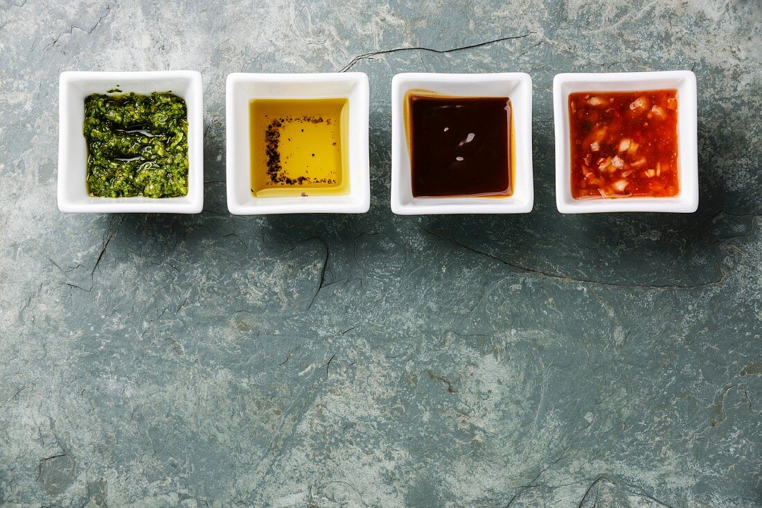 Different sauces green salsa, mignonette, oyster sauce and pepper oil on stone slate background