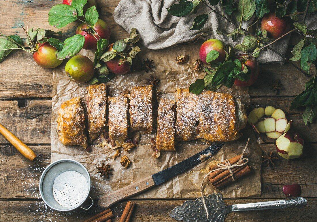 Apple strudel with cinnamon and sugar powder cut in slices served with star anise, nuts and fresh apples