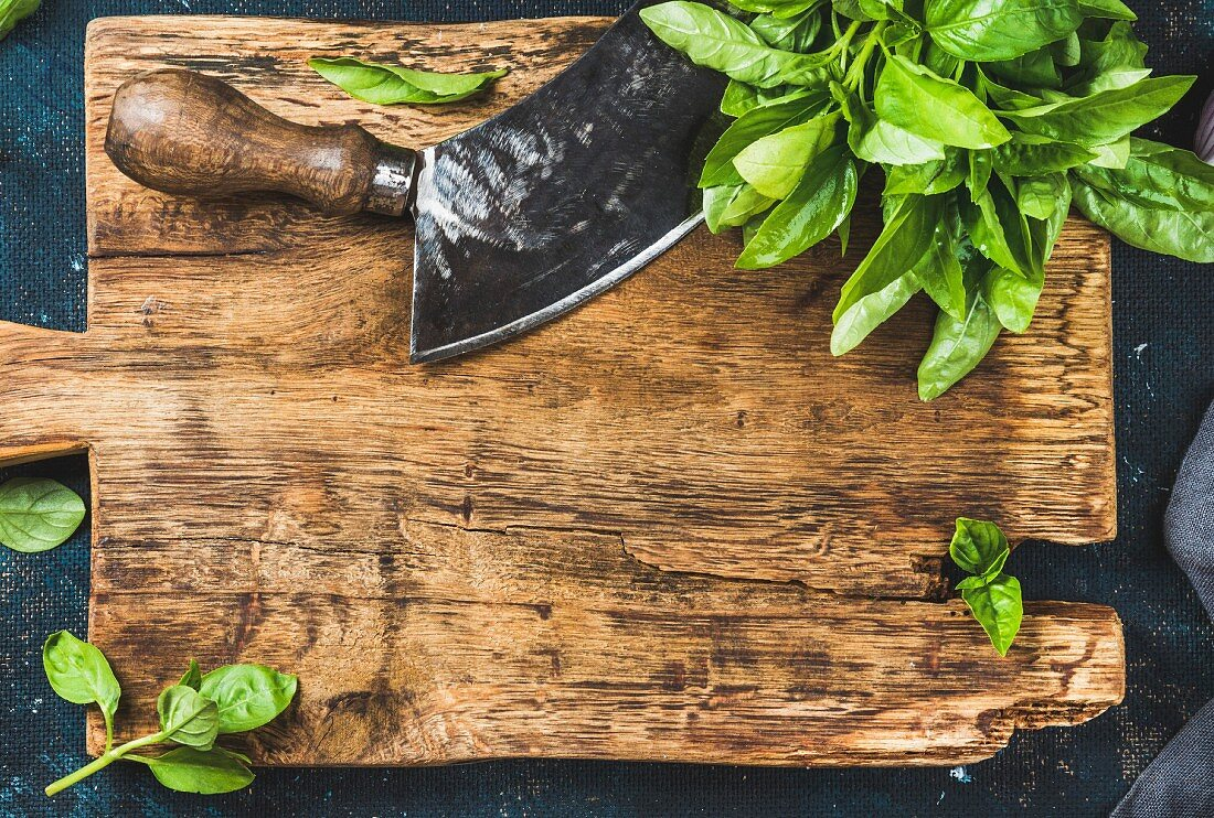 Fresh green basil and vintage herb chopper on rustic wooden bord