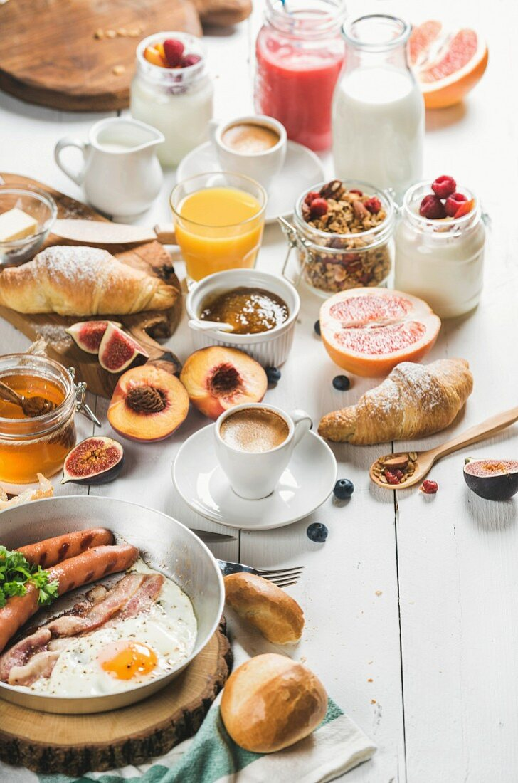 Fried egg with sausages and bacon, bread, croissants, jam, butter, fruits, smoothie, orange juice, yogurt, granola, milk and coffee