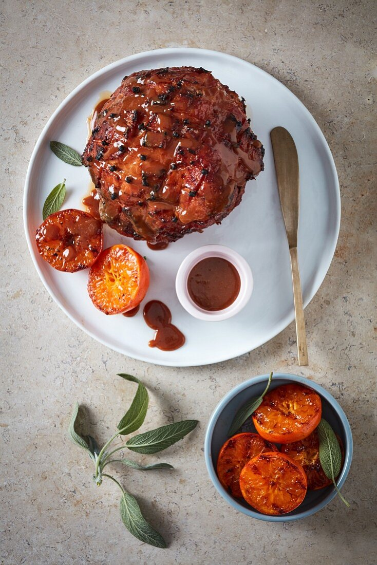 Studded baked ham with a toffee glaze and grilled clementines