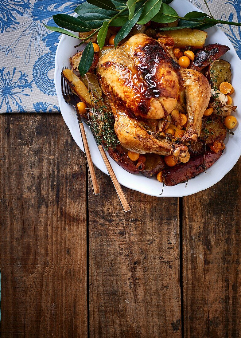 Roast chicken stuffed with thyme and physalis on a bed of sweet potato