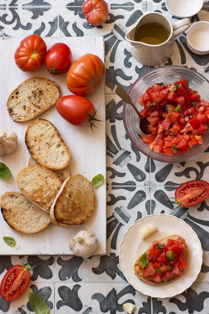 Ingredients for bruschetta al pomodoro (tomatoes, bread, garlic, olive oil and salt)