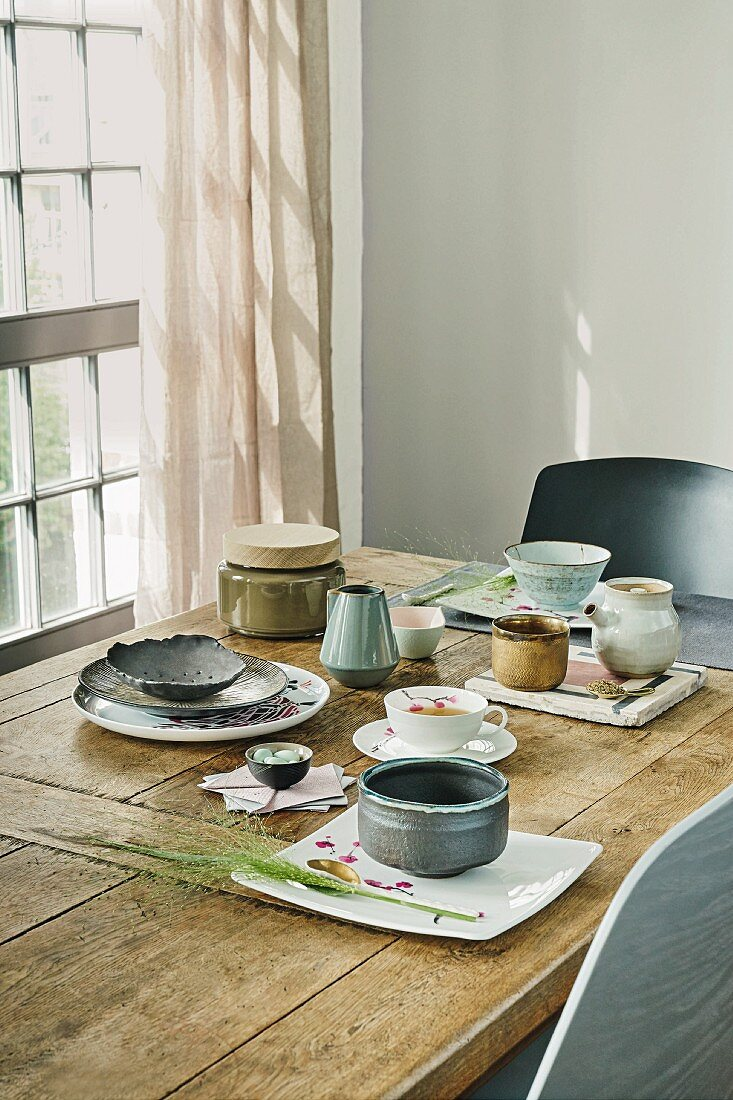 A tea table set in Asian style with ceramic and porcelain crockery