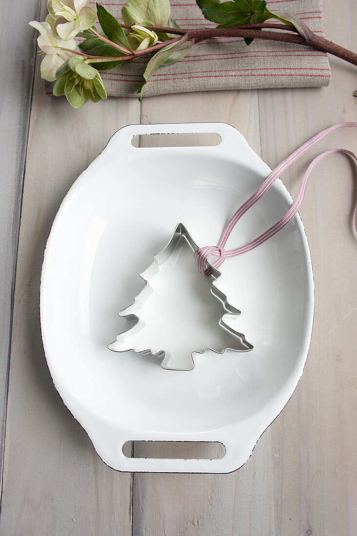 A Christmas tree cutter and a ribbon in an enamel baking dish