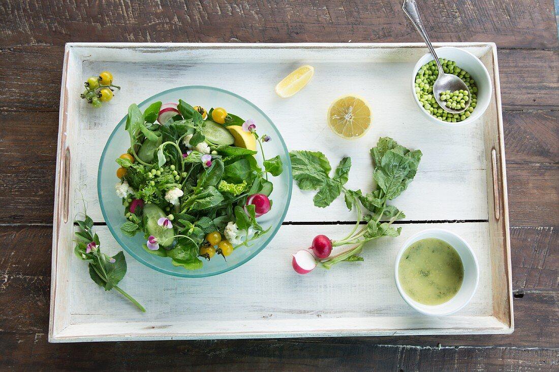 Vegan mixed garden salad on a wooden tray