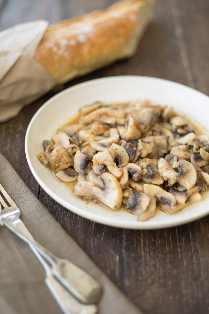 Marinated mushrooms on a plate served with a baguette