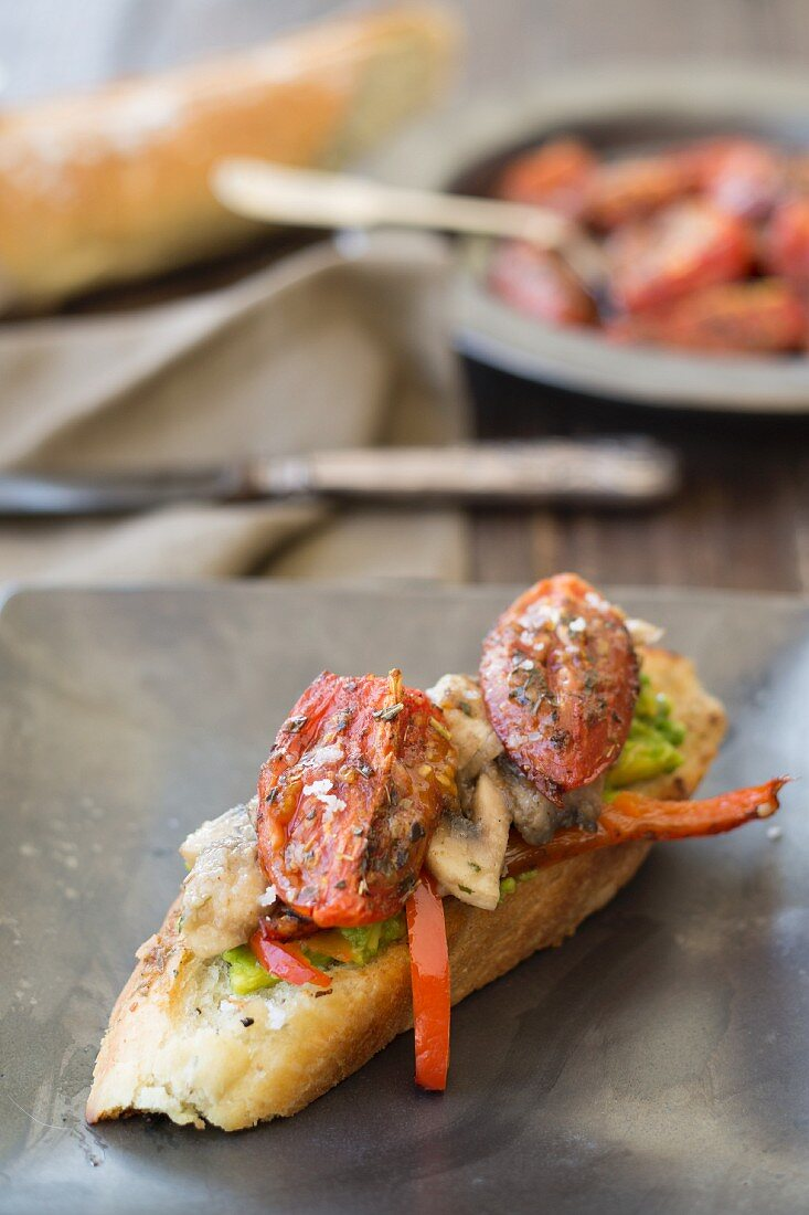 A crostini with tomato, mushroom, avocado and red pepper (vegan)