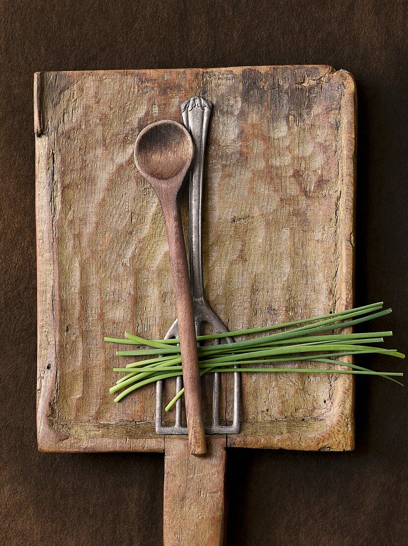 A spatula and an old wooden spoon with chives (seen from above)