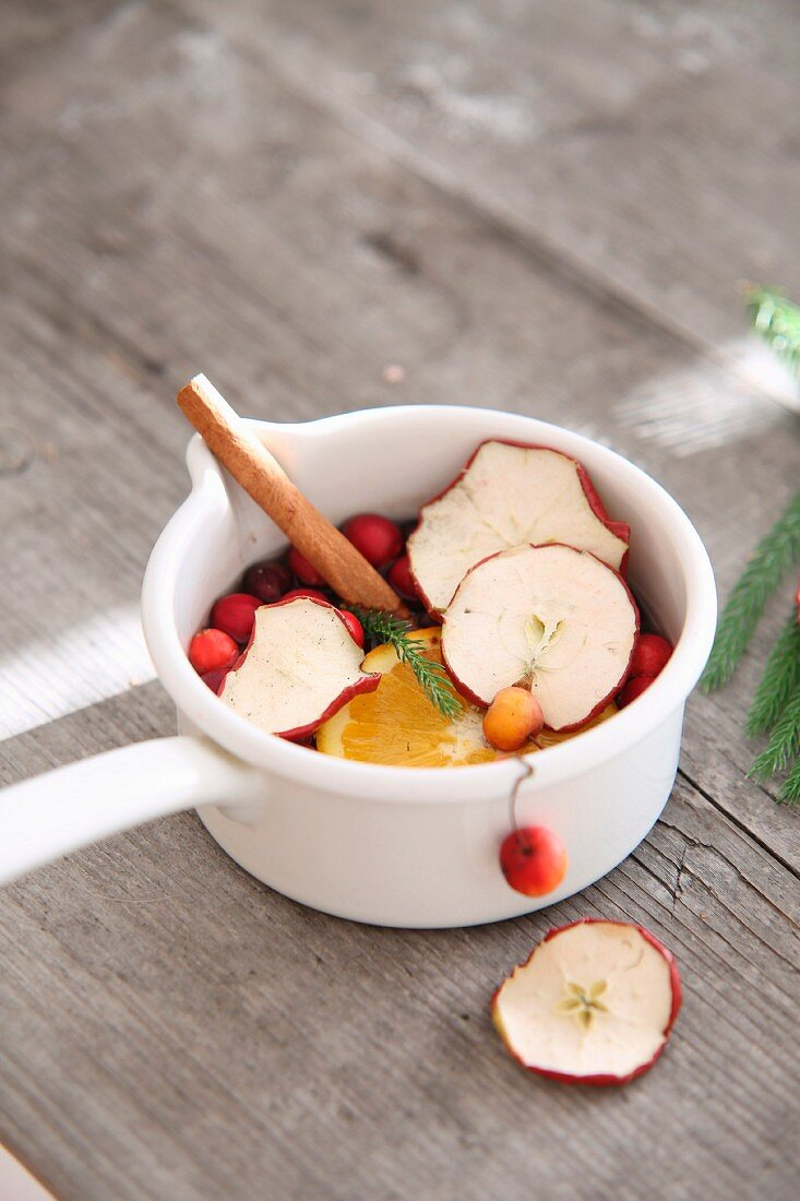 Christmas pot pourri made from slices of apple and orange, crab apples and cinnamon in casserole dish