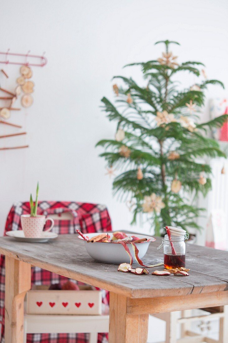 Jar of honey, dried apple slices, bowl and cups on wooden table in front of small Christmas tree with straw stars