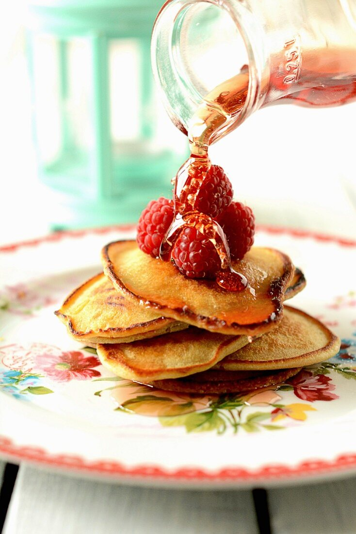 Maple syrup being poured over pancakes with raspberries
