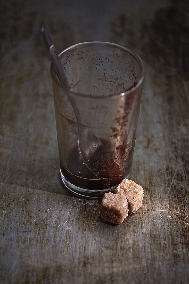 Coffee residues in a glass with cubes of brown sugar in front of it
