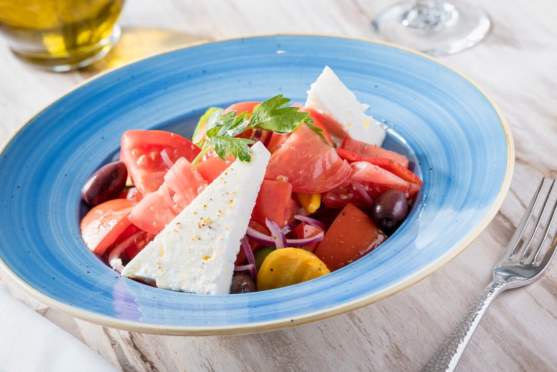Tomato salad with feta cheese, Kalamata olives, red onion and yellow pepper