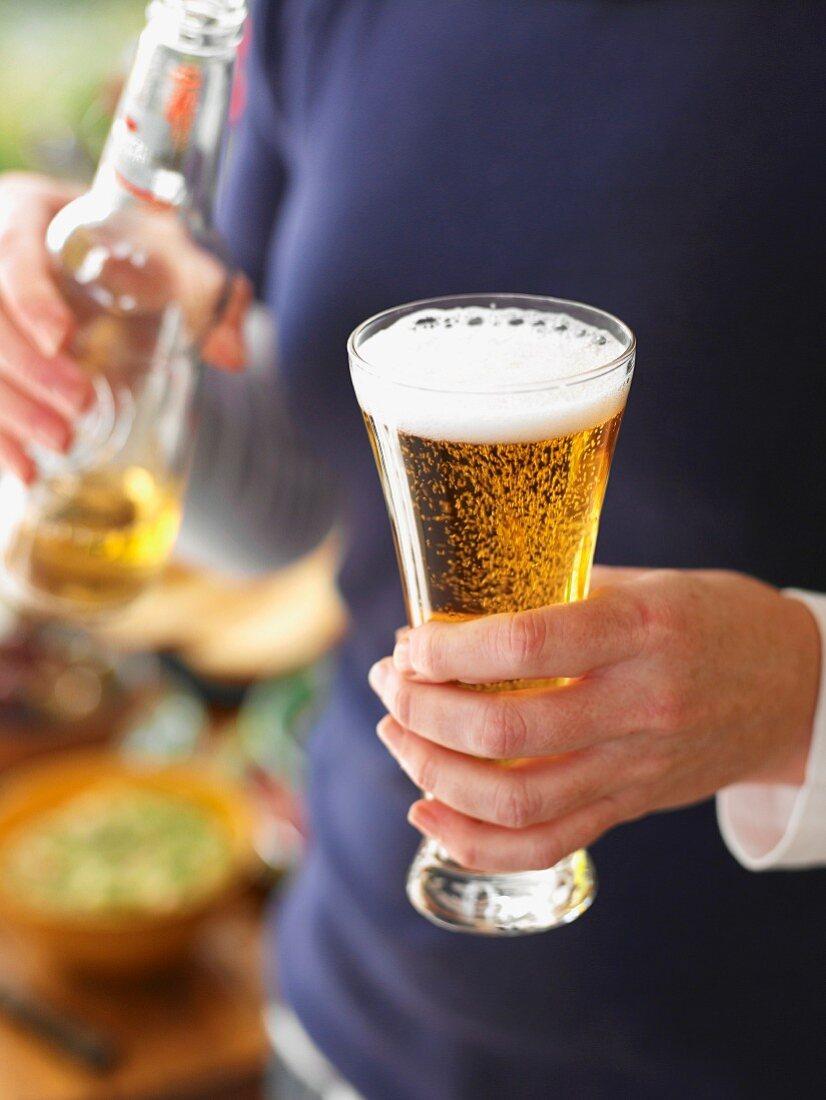 Mann mit Sagres-Bier in Bierglas und Bierflasche (Portugal)