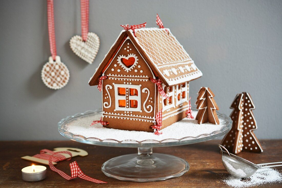 A gingerbread house on a cake stand, decorated with icing