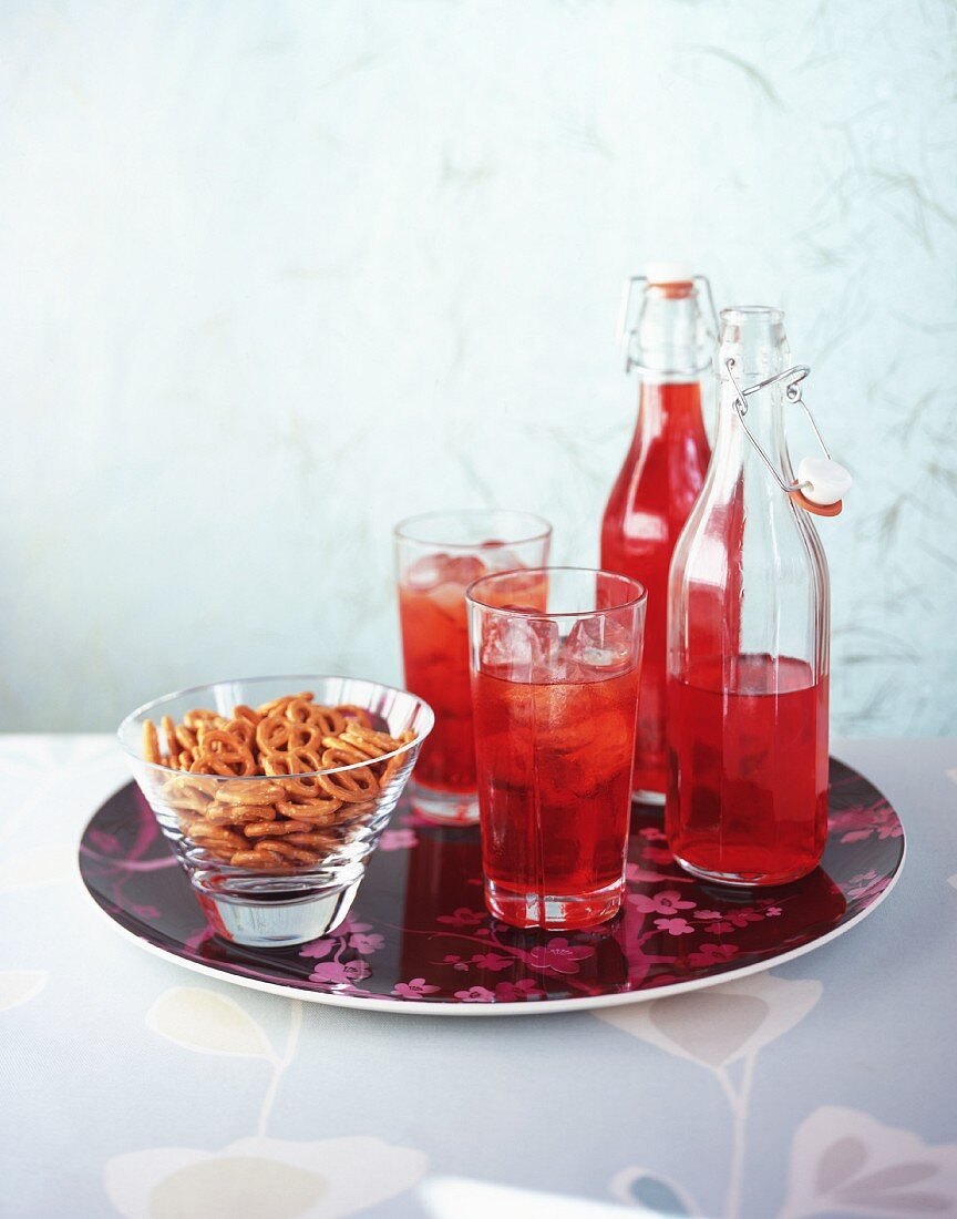 Glasses and bottles of red juice and a bowl of pretzels