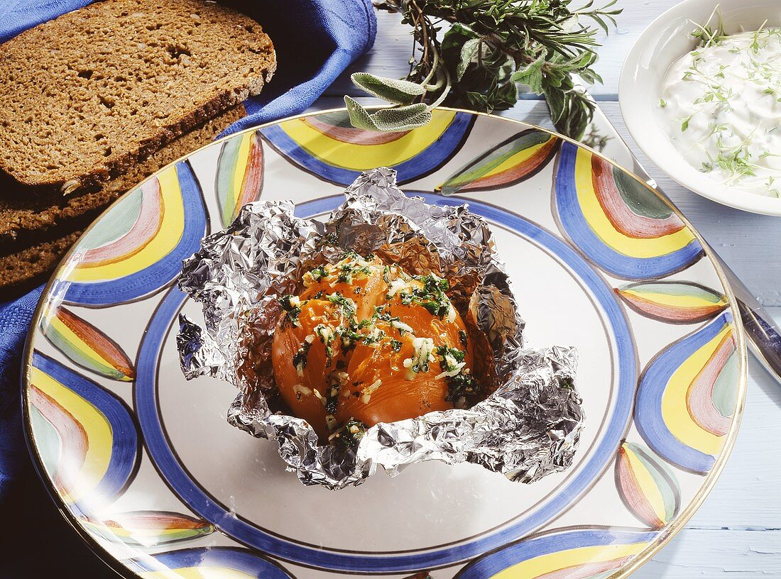 Grilled tomato with herb & garlic sauce in aluminium foil