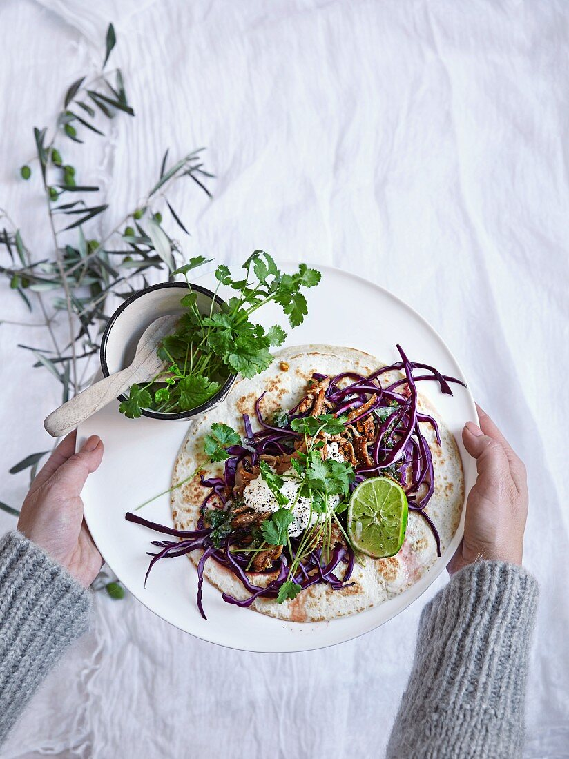 A tortilla with sliced beef, red cabbage and coriander