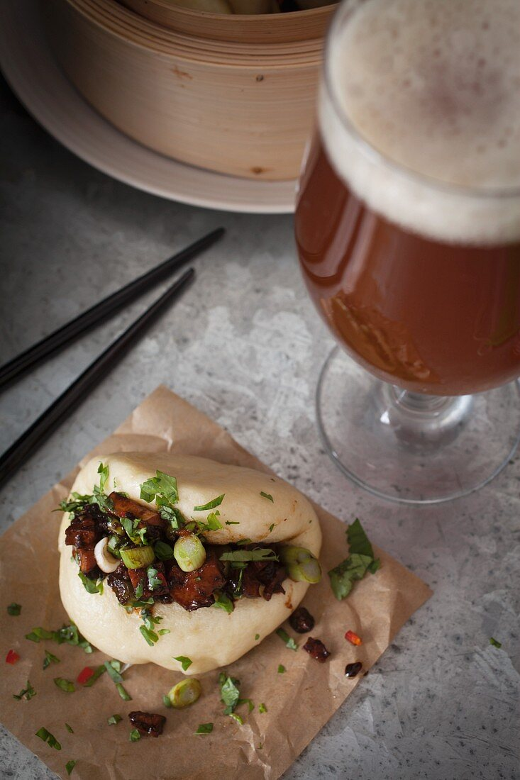 Vegan steamed bao bun filled with smoked tofu and chestnut mushrooms marinated in soy, sesame oil, chilli sauce and garlic, topped with sliced spring onions, corriander and red chilli