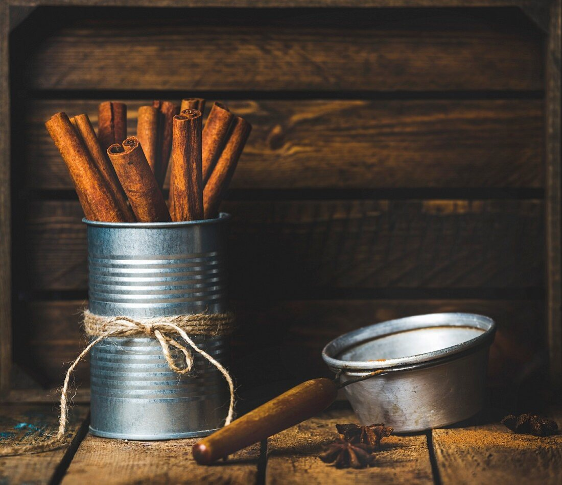 Cinnamon sticks in a tin tied with string, anise stars and a sieve on a rustic wooden background