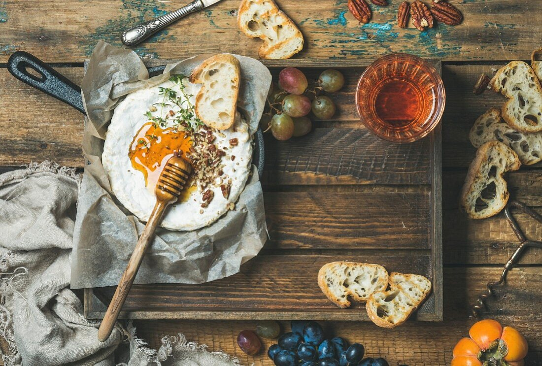 Camembert cheese with honey and herbs in small pan, baguette slices, grapes and glass of rosé wine