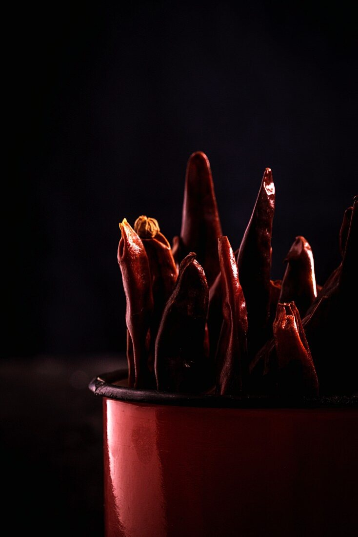 Spicy red chillies in cup on old wooden table