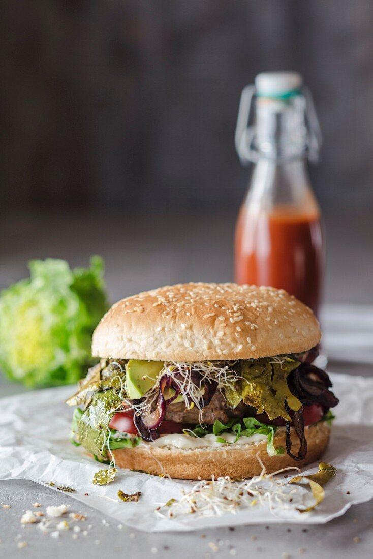 A hamburger with seaweed bacon, bean sprouts and strawberry ketchup