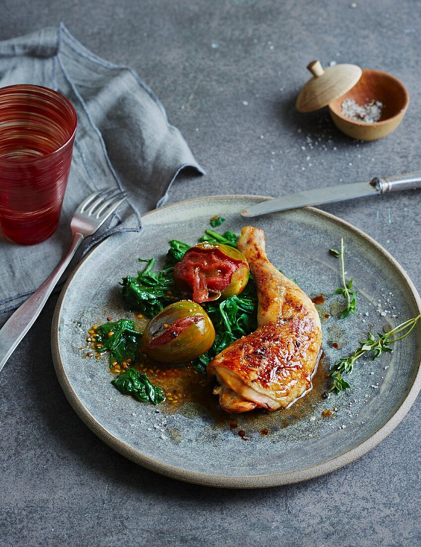 Oven-grilled leg of chicken with braised tomatoes on a bed of dandelion spinach (low carb)
