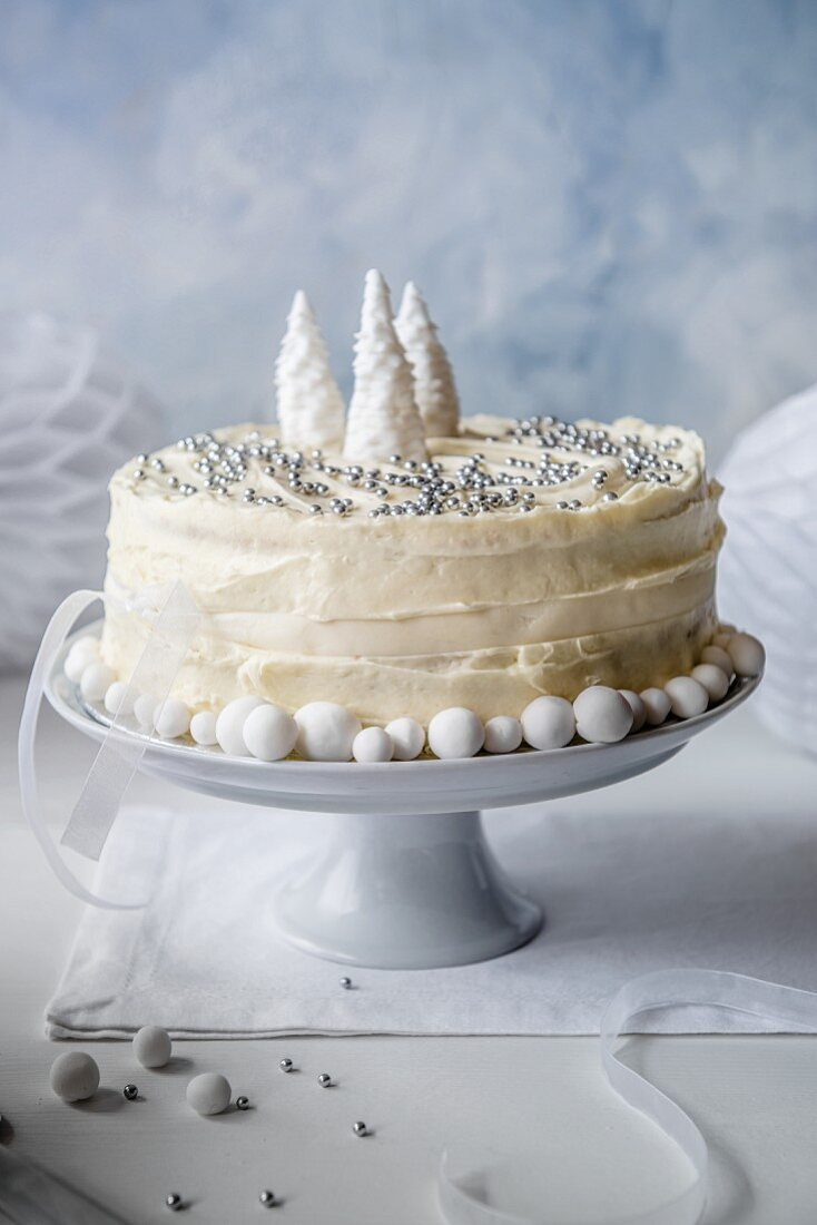 A Christmas cake with white chocolate icing, decorated with silver beads