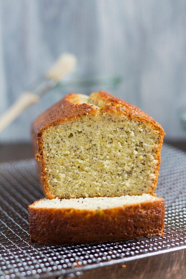 A lemon and poppyseed loaf cake on a wire cooling rack (with one slice cut off)