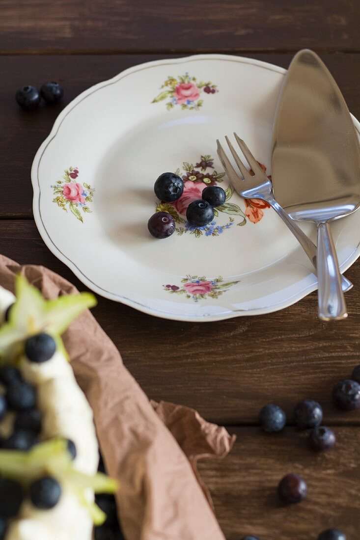A citrus and blueberry cake next to blueberries on a plate