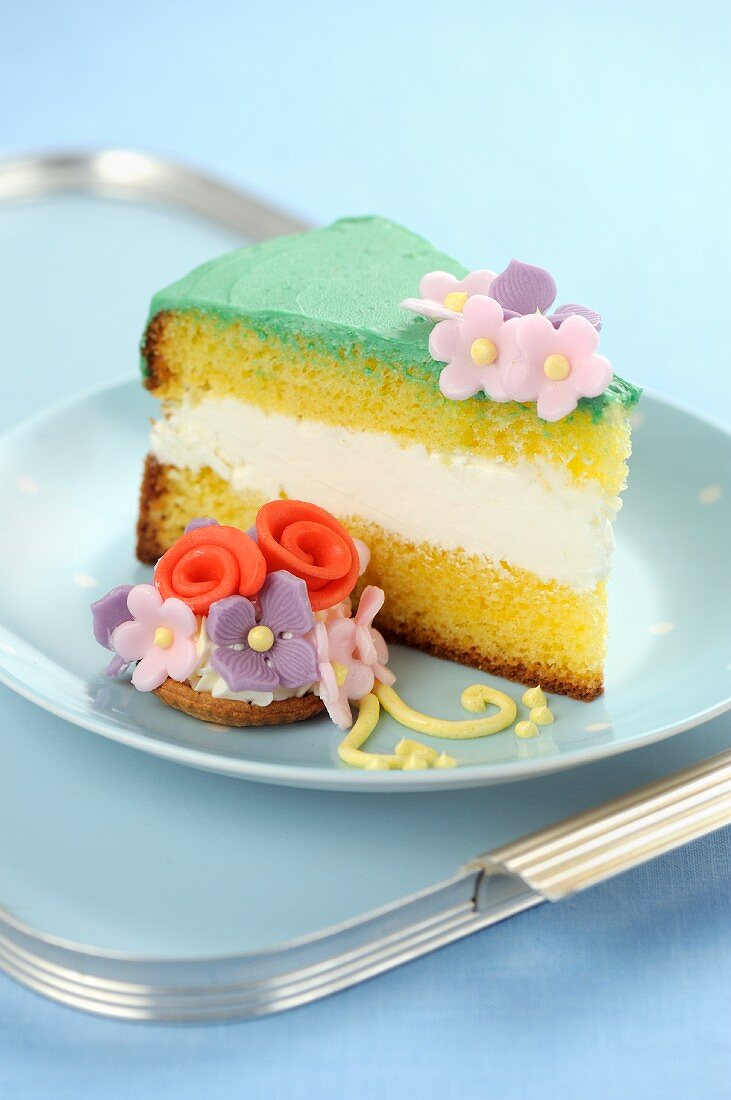 A piece of Genoese cake with fondant flowers
