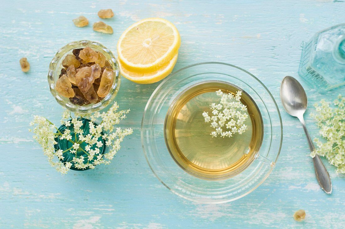 Elderflower tea in a cup, elderflowers, lemon slices and rock sugar