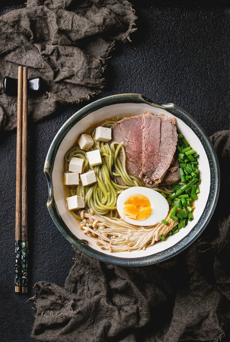 Bowl of asian style soup with green tea soba noodles, beef, egg, mushrooms, spring onion and tofu cheese