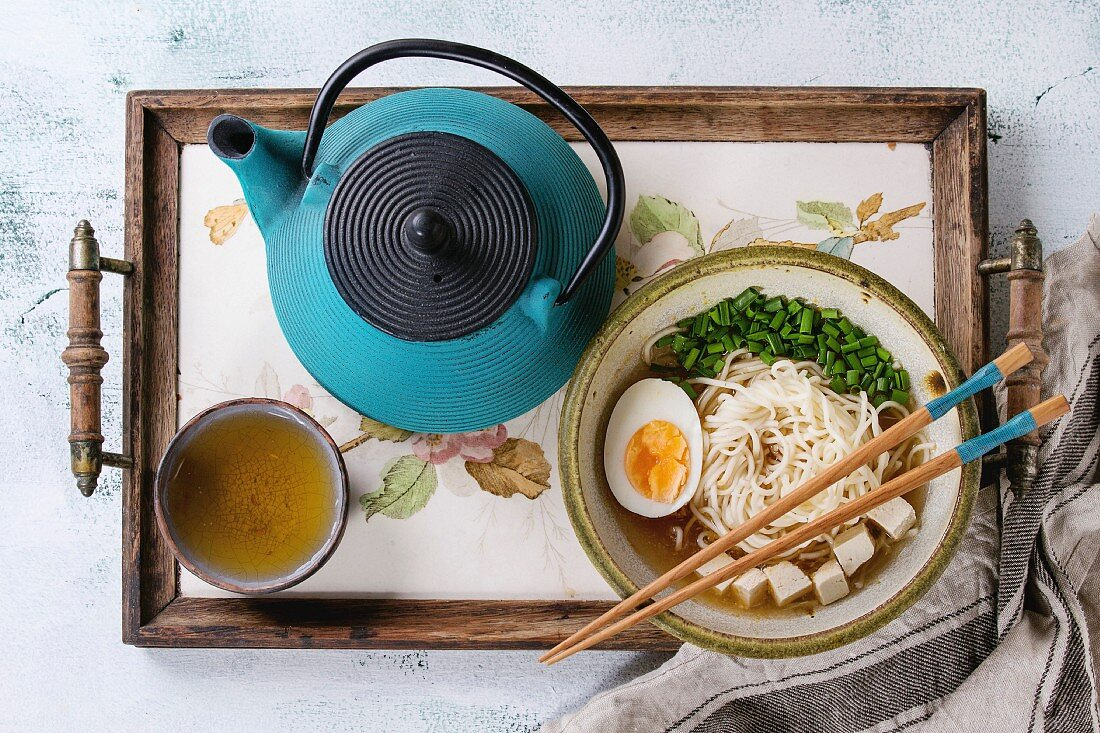 Bowl of asian style soup with noodles, egg, spring onion and tofu cheese, teapot and cup of green tea