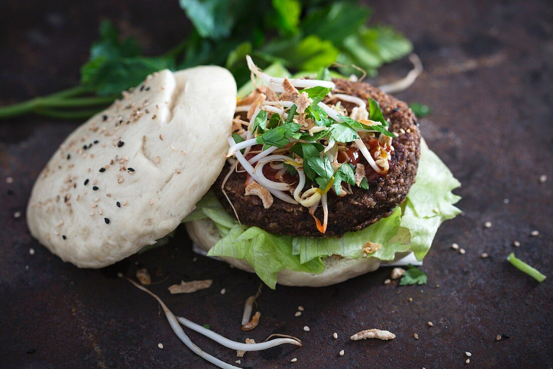A 'gua bao' bun with a vegan bean burger, mung bean sprouts, fried onions and lettuce (vegan)