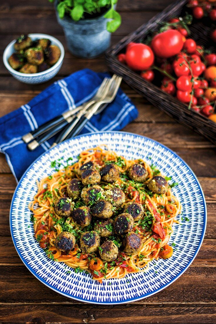 Vegan aubergine meatballs on a bed of spaghetti with tomato sauce and olives