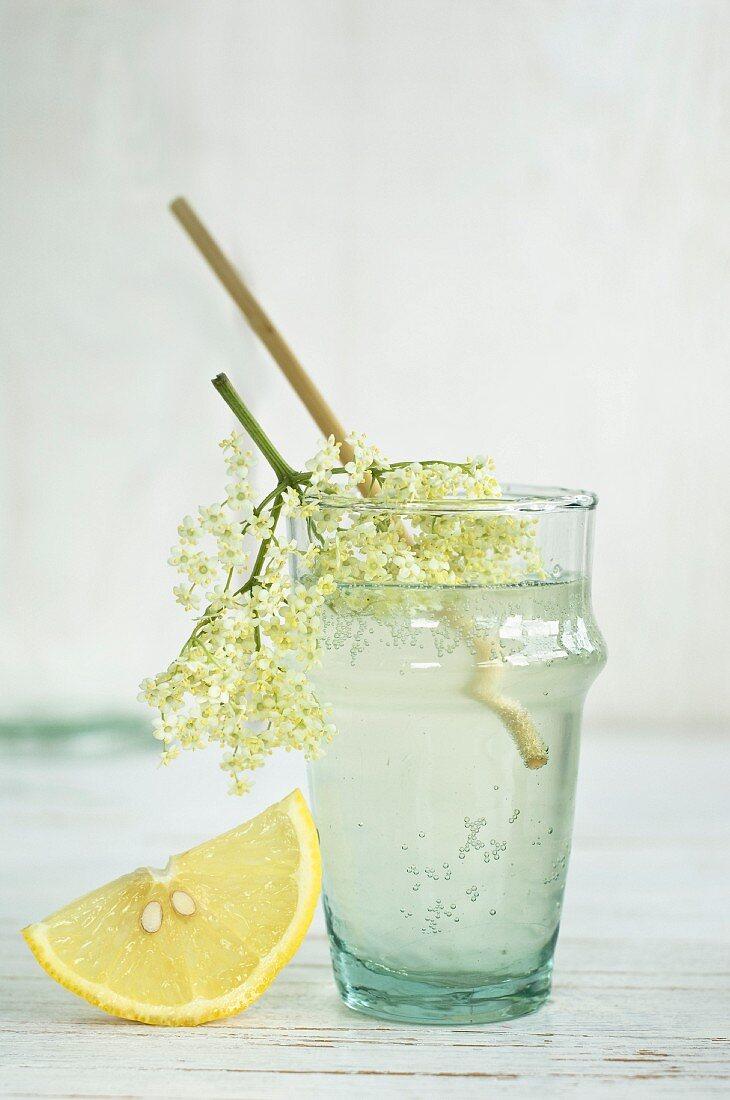 An elderflower drink in a glass with a straw, elderflowers and a wedge of lemon