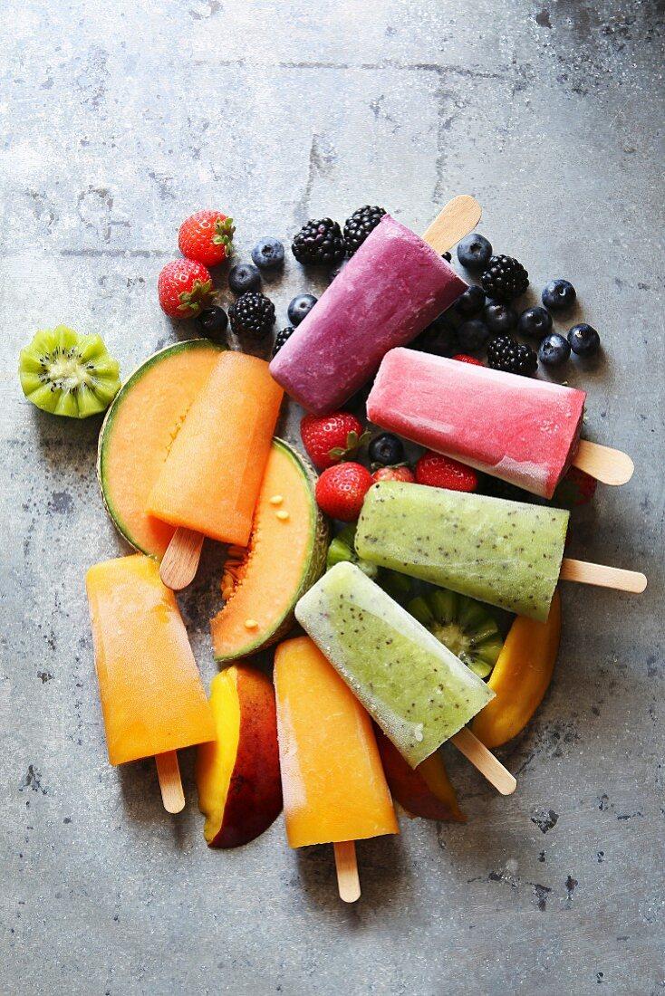 Popsicles with kiwi, mango, cantaloupe, blueberry, blackberry and strawberry over fresh fruit